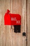 Cassetta delle lettere rossa sulla porta d'annata di legno Fotografia Stock