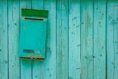 Cassetta delle lettere verde su un recinto di legno di legno fotografie stock