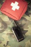 Cassetta di pronto soccorso e radio portatile su un tessuto con il picchiettio del cammuffamento immagini stock