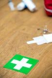 Cassetta di pronto soccorso ed incrocio verde su una superficie di legno Fotografia Stock