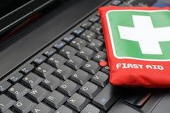 Cassetta di pronto soccorso sulla tastiera del computer portatile fotografia stock libera da diritti