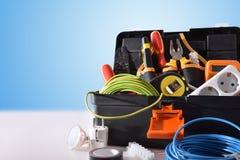 Cassetta portautensili in pieno degli strumenti e del materiale elettrico sulla tavola bianca fotografia stock