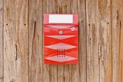 Cassetta postale rossa sulla vecchia parete di legno fotografie stock