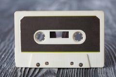Cassette compacte de vintage avec le format de enregistrement sur bande magnétique pour l'audio et le playback Fond en bois gris  image libre de droits