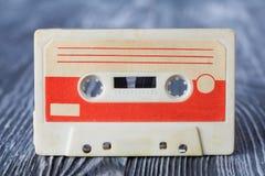 Cassette compacte rouge avec le format de bande magnétique pour l'enregistrement audio et le playback Fond en bois gris Orientati photographie stock libre de droits