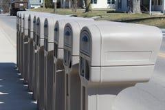 Cassette delle lettere identiche in una fila fotografia stock