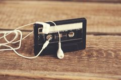 Cassette with earphone. Retro tape cassette with earphone on table stock photos