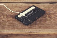 Cassette with earphone. Retro tape cassette with earphone on table stock photo