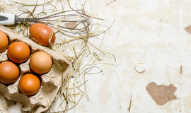 The cassette with eggs, hay and whisk . Stock Photo