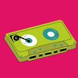 Cassette. Green cassette on pink background Royalty Free Stock Photo