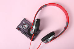 Cassette and headphones. Old cassette and red headphones on a pink background Royalty Free Stock Image