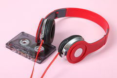 Cassette and headphones. Old cassette and red headphones on a pink background Royalty Free Stock Images