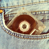 Cassette in the Jeans. Toned Photo of Vintage Audio Tape Cassette in the Jeans Pocket closeup stock image