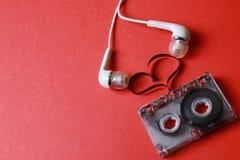 Cassette met het hart van de bandvorm op rood stock foto's