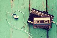 Cassette and old tape player over wooden background. retro filter Royalty Free Stock Photos
