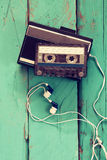 Cassette and old tape player over wooden background. retro filter.  royalty free stock photo