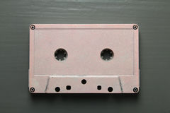 Cassette. One old pink cassette on a black wooden background royalty free stock photos