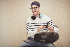 Cassette rewind. Young man rewinding cassette with pencil, isolated on brown stock photography