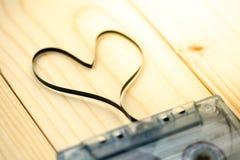 Cassette sonore avec la bande magnétique dans la forme du coeur sur le dos en bois Image libre de droits