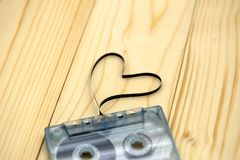 Cassette sonore avec la bande magnétique dans la forme du coeur sur le dos en bois Images libres de droits