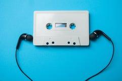 cassette sonore de cru avec les écouteurs noirs sur b bleu image libre de droits