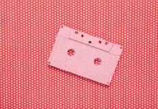 Cassette sonore en pastel de rose sur un fond rouge créatif photographie stock libre de droits