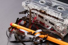 Cassette sonore et crayon sur une table noire Vieux support d'informations magnétique images stock