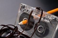 Cassette sonore et crayon sur une table noire Vieux support d'informations magnétique photo libre de droits