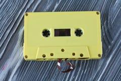 Cassette sonore jaune sur le fond en bois gris photographie stock