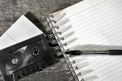 Cassette tape and blank notebook on table Stock Images