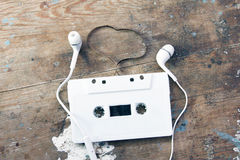 Cassette tape with headaet. On rusty wooden background Royalty Free Stock Photo