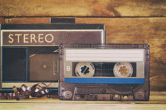 Cassette tape and old player over wooden table. retro filter Royalty Free Stock Photos