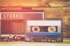 Cassette tape and old player over wooden table. retro filter Stock Photo