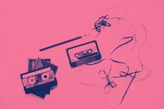 Cassette tape over white background with tangled ribbon. Top view cassette tape over white background with tangled ribbon with pencil to rewind duotone stock photo