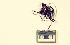 Cassette tape over wooden table with tangled ribbon. top view. retro filter Royalty Free Stock Photos
