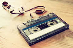 Cassette tape over wooden table with tangled ribbon. top view. retro filter.  stock photo
