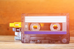 Cassette tape over wooden table with tangled ribbon. top view. retro filter.  stock image