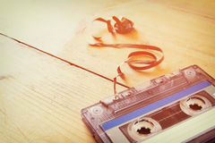 Cassette tape over wooden table with tangled ribbon. top view. retro filter Royalty Free Stock Image