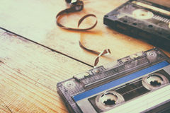 Cassette tape over wooden table with tangled ribbon. top view. retro filter Stock Photography