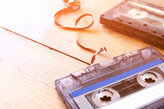 Cassette tape over wooden table with tangled ribbon. top view. retro filter Royalty Free Stock Photo