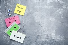 Cassette tapes with earphones. And inscription Music Day on wooden table royalty free stock photo