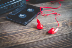 Cassette tapes and player over wooden table. Royalty Free Stock Images