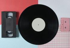 Cassette vidéo, disque vinyle, cassette sonore sur un fond créatif, vue supérieure image libre de droits
