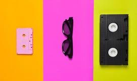 Cassette vidéo, lunettes de soleil, cassette sonore sur un multicolore image stock