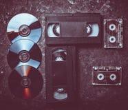Cassettes vidéo de configuration plate, CD& x27 ; s, cassette sonore sur un concre noir photographie stock libre de droits