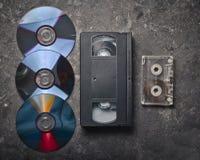 Cassettes vidéo de configuration plate, CD' ; s, cassette sonore sur une surface en béton noire Rétro technologie de media du image libre de droits