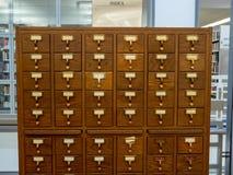 Cassetto di catalogo di legno della biblioteca della quercia che si siede in una biblioteca moderna immagini stock libere da diritti