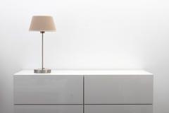 Cassettone bianco con la lampada da tavolo nell'interno luminoso di minimalismo Fotografie Stock Libere da Diritti