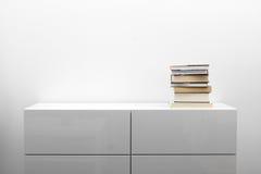 Cassettone bianco con la pila di libri nell'interno luminoso di minimalismo Immagine Stock