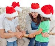 Casseurs d'ouverture de famille ensemble sur le sofa Photos stock